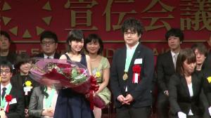 第52回宣伝会議賞グランプリに輝いた、渡辺幸一さん(右)と、花束を贈呈する女優の小芝風花さん(左)。