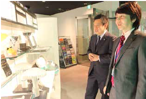 本社のショールームにて、広報宣伝室の大木昌一室長(写真右)と筆者。技術力を伝える発信拠点としても機能しているスペース。